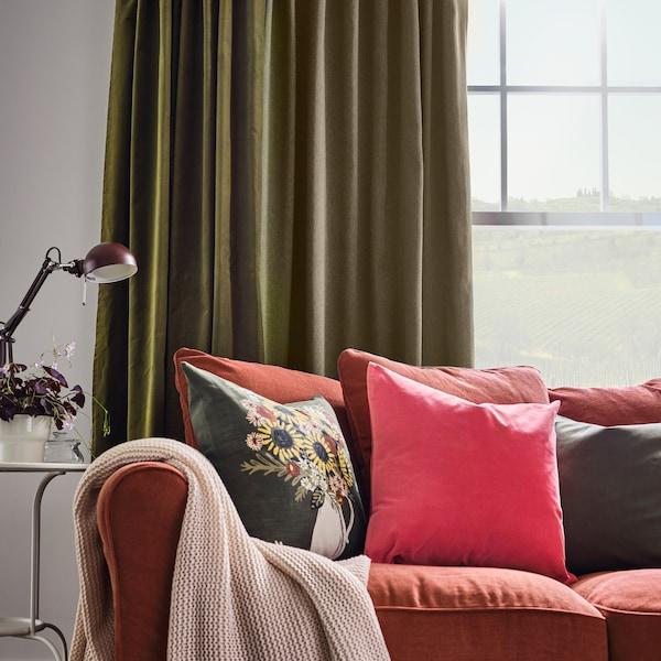 Jasnoczerwona sofa z czerwono-pomarańczową i dwoma ciemnozielonymi poduszkami oraz bladoróżowym pledem. Na oknie za sofą wiszą zielone zasłony.