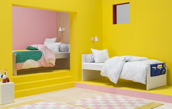 Jasnoróżowa i żółta sypialnia z dwoma pojedynczymi łóżkami z kolorowymi, graficznymi narzutami.