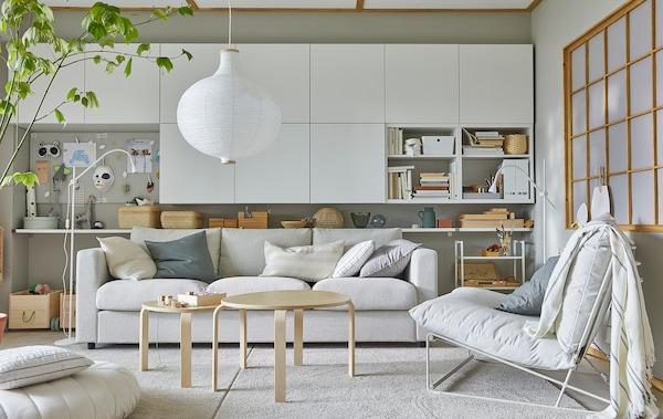Jasny pokój z krzesłem HAVSTA, wieloma białymi szafkami ściennymi i okrągłą, białą lampą wiszącą.