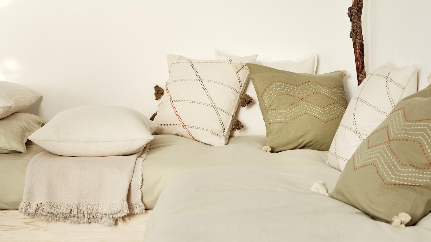 Jastučići u različitim navlakama, uključujući prljavobele HERVOR navlake jastučića i zelene HALLVI navlake jastučića, na krevetima.