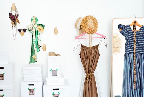 جدار لتخزين الملابس مع إكسسوارات على خطافات خشبية وصناديق أحذية وفساتين وقبعات على حامل معطف ومرآة طويلة.