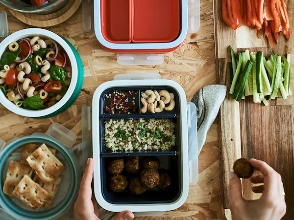 Jedlo ukladané do krabičiek. V jednej krabičke je niekoľko oddelení vyplnených rôznym jedlom, vedľa je krabička s chlebom a ďalšie s cestovinovým šalátom.