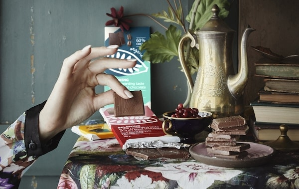 Jemand greift ein Stück Schokolade von einem Tisch mit Schokolade, Büchern und Obst.