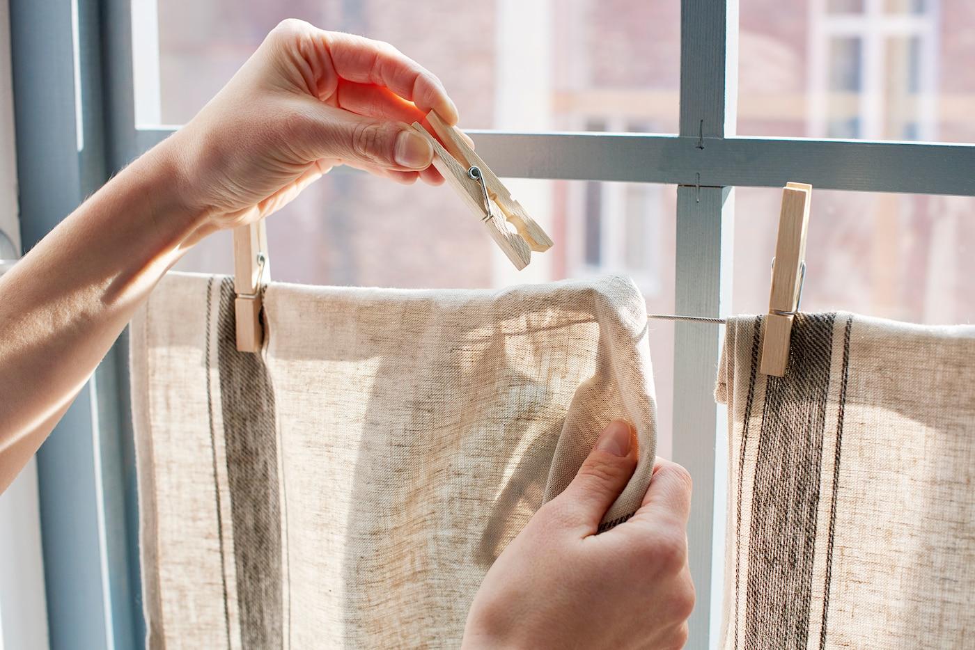 Jemand hängt 2 Geschirrtücher an einem Draht vor einem Fenster auf & befestigt sie mit Wäscheklammern.