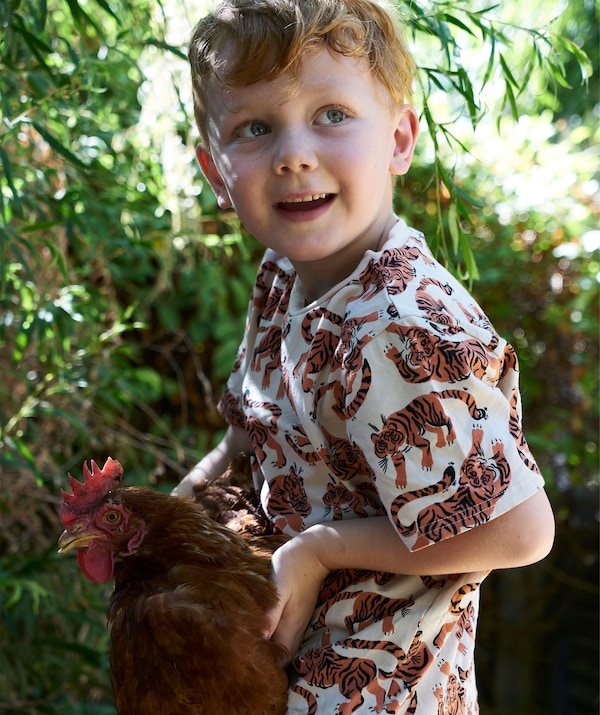 Jeune enfant tenant une poule.