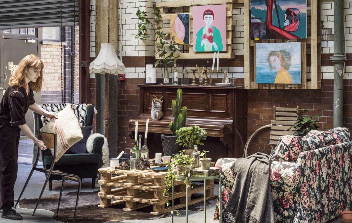 Jeune femme dans un salon commun, équipé de meubles de styles variés et de plantes.