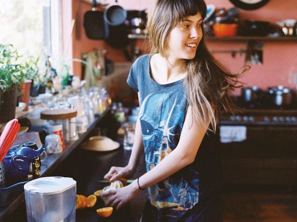 Jeune femme se retournant pour regarder quelqu'un pendant qu'elle lave et coupe des morceaux de fruits à côté de l'évier de la cuisine.