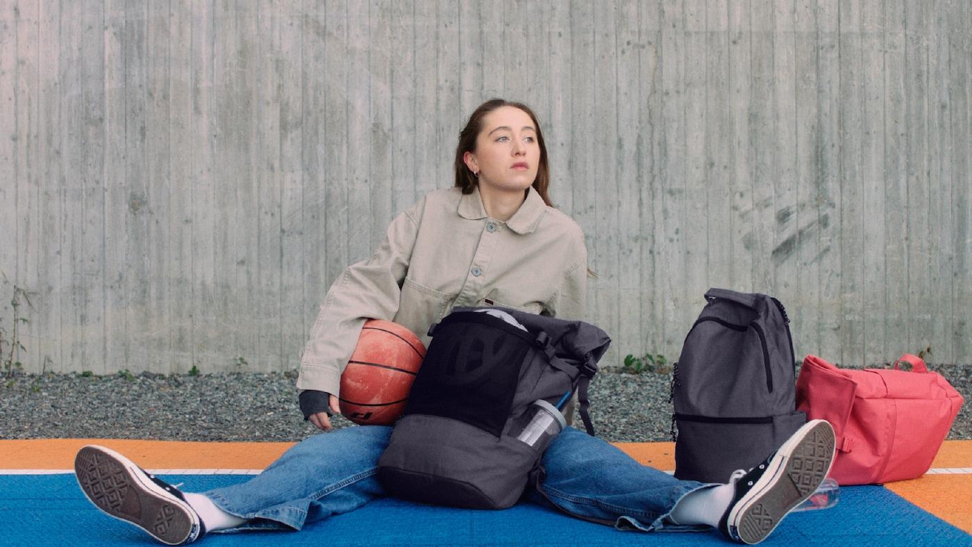 Jeune femme tenant un ballon de basket, assise sur le sol d'un terrain de basket avec à côté d'elle les sacs DRÖMSÄCK, VÄRLDENS et STARTTID.