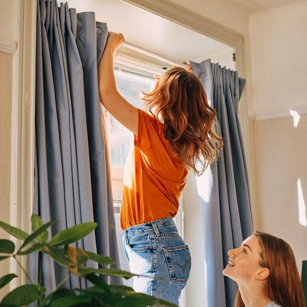 jeune fille qui installe une tringle a rideaux avec une amie