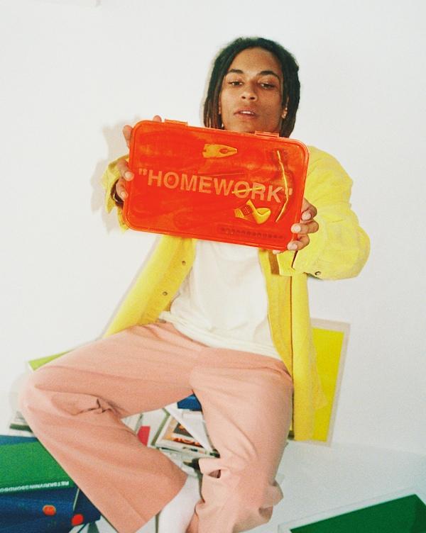 """Jeune homme aux vêtements multicolores portant une trousse à outils IKEA orange décorée du mot """"HOMEWORK""""."""