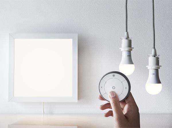 جهاز التحكم عن بُعد الذكي TRÅDFRI مع لوحة إضاءة واثتنان من لمبات الإضاءة.