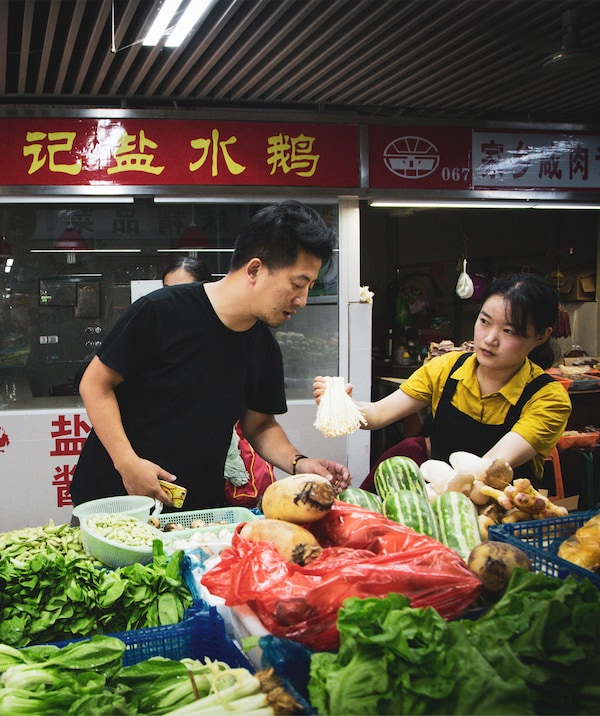 Jiaqin stands at a vegetable stall.
