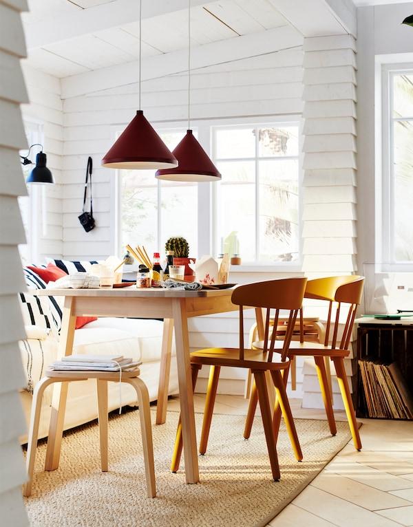 Jídelna s pohovkou plnou polštířů, stolem s židlemi a stoličkami KYRRE z březového dřeva.
