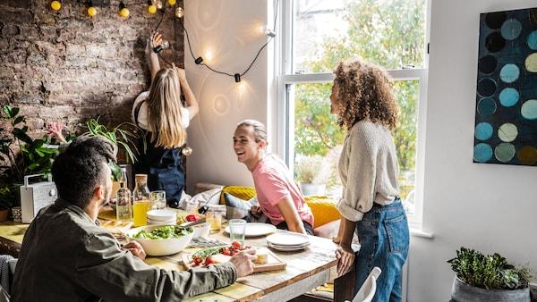 Jídelna, v níž se 4 lidé chystají usednout k prostřenému stolu.