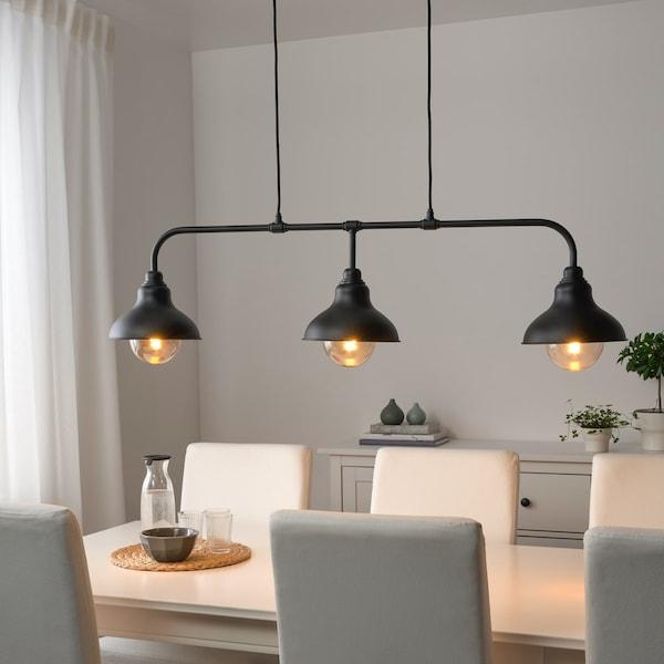 Jídelní stůl se šesti čalouněnými židlemi a ze závěsným osvětlením se třemi lampami.