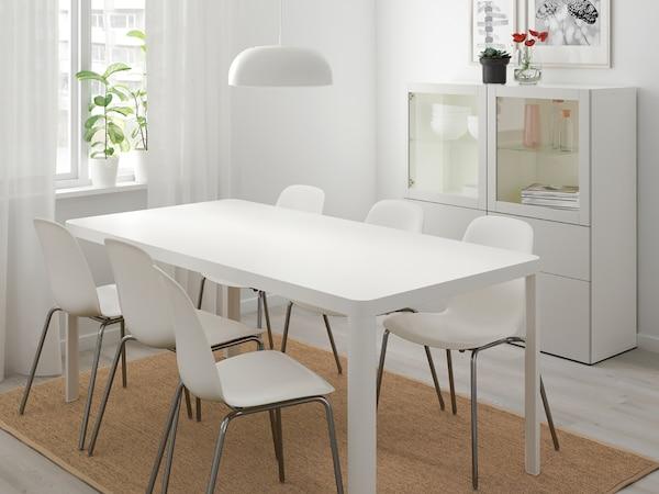 Jídelní židle a stůl v bílé barvě, bílý sekretář v pozadí.