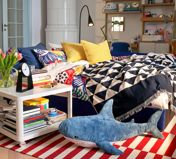 JOHANNE jacquard woven throw with decorative pattern, over a bed sofa, with a lamp, bed-side table with lots of books on it.