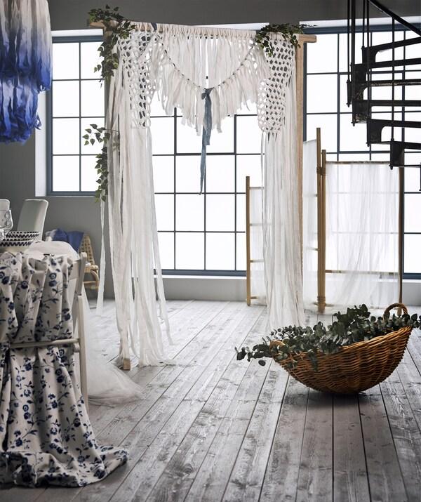 Jolie déco en arrière-plan composée du paravent en rotin TÄNKVÄRD drapé de pièces de coton blanc.