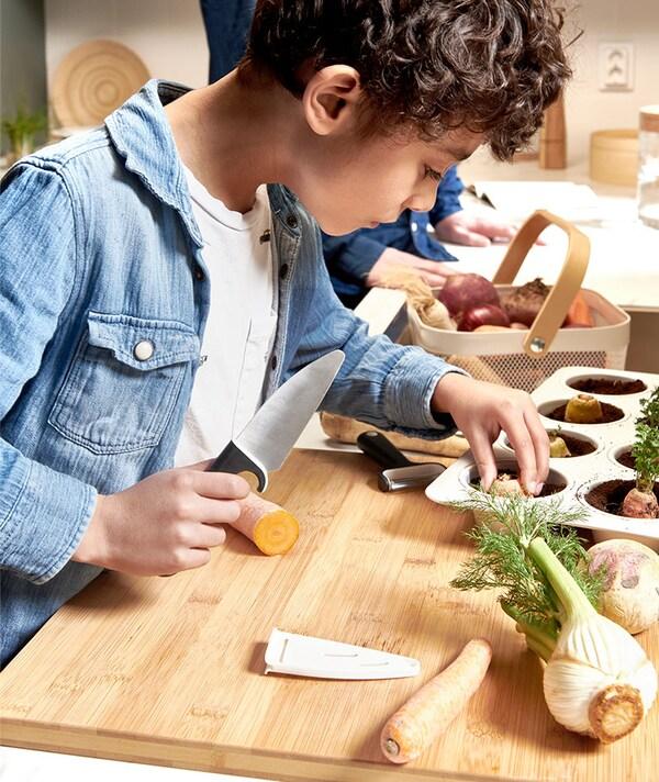 Jongen is groenten aan het snijden