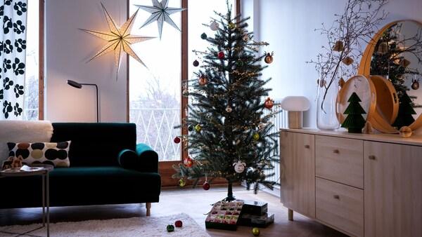 Joulukuusi olohuoneessa, kuusen alla muutamia joululahjoja