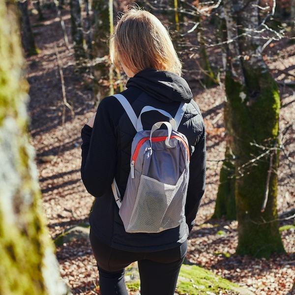 Jovem caminha numa encosta iluminada pelo sol com algumas árvores, com uma mochila PIVRING em cinzento claro.