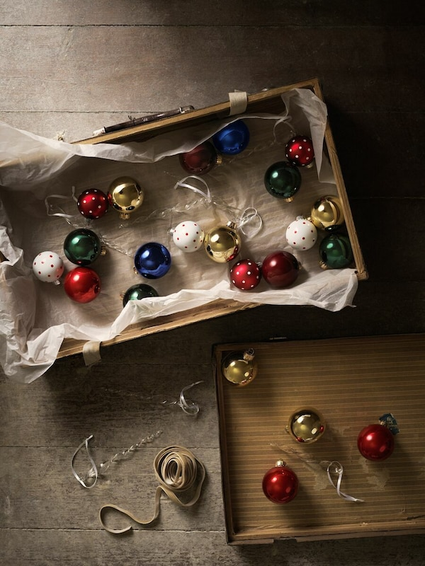 Julekugler i en papkasse, der er ved at blive hængt op.