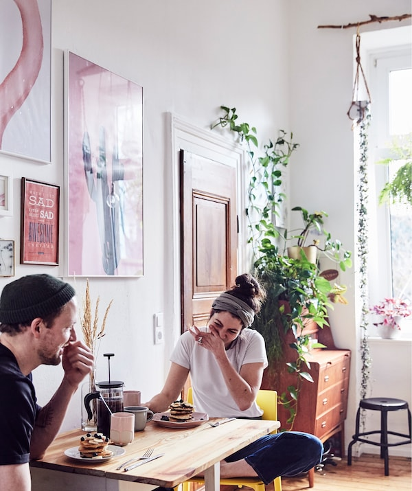 Julia and André eating breakfast at a drop-leaf table in a room with plants and artwork on the walls.