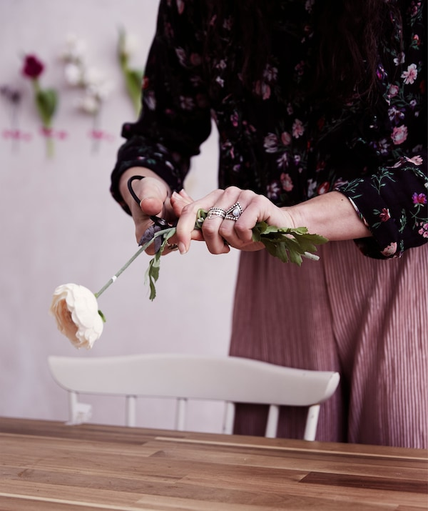 Julia cuts the stem of an artificial rose over a wooden table top.