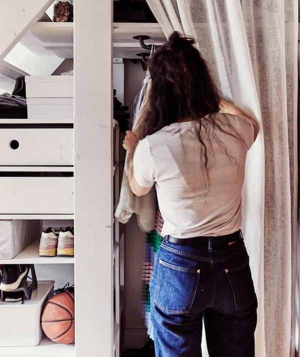 Julia greift nach Kleidung, die sich hinter einem Vorhang unter der Treppe befindet.