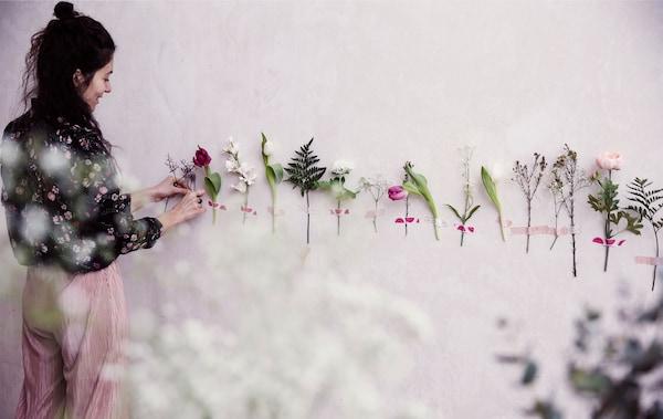 Julia ha pegado con cinta adhesiva tallos de flores en línea a lo largo de una pared blanca.