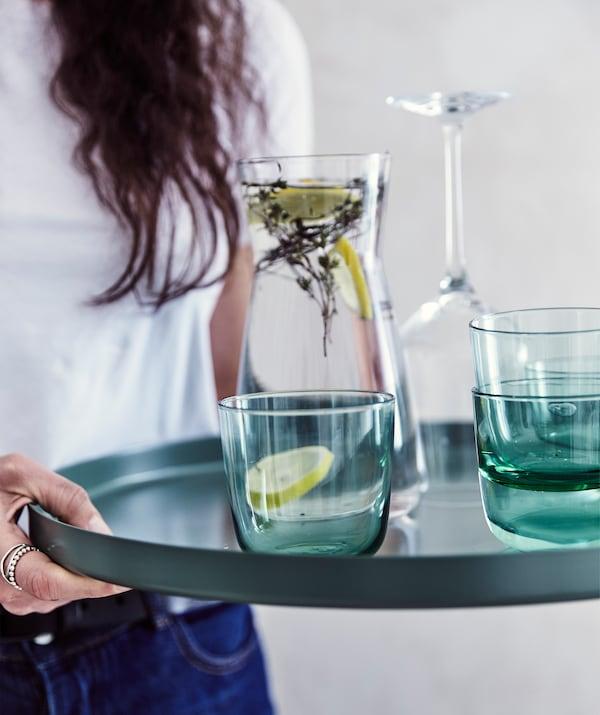 Julia hält das Tablett des GLADOM Tabletttischs in Dunkelgrün in Händen, darauf sind eine Karaffe mit Wasser und mehrere Gläser zu sehen.