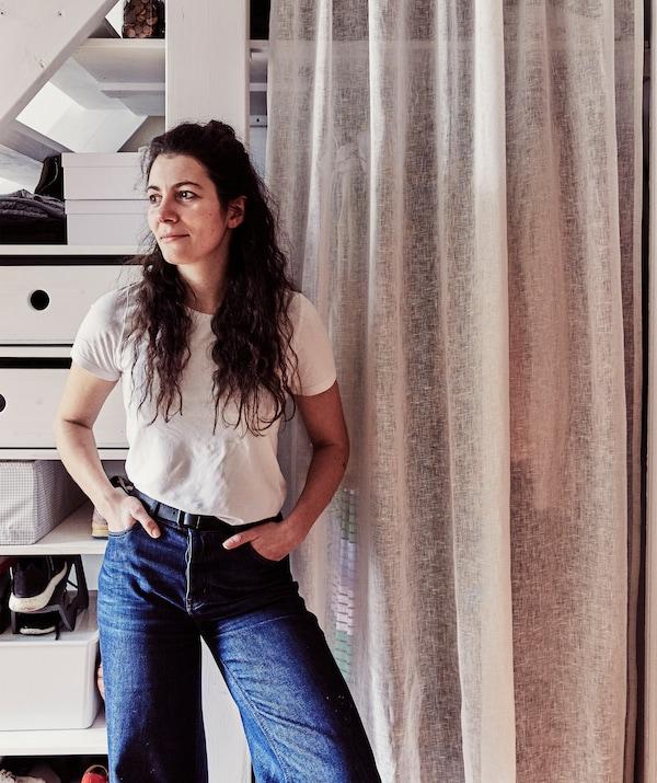 Julia stoji ispred rješenja za odlaganje odjeće iza zavjese.