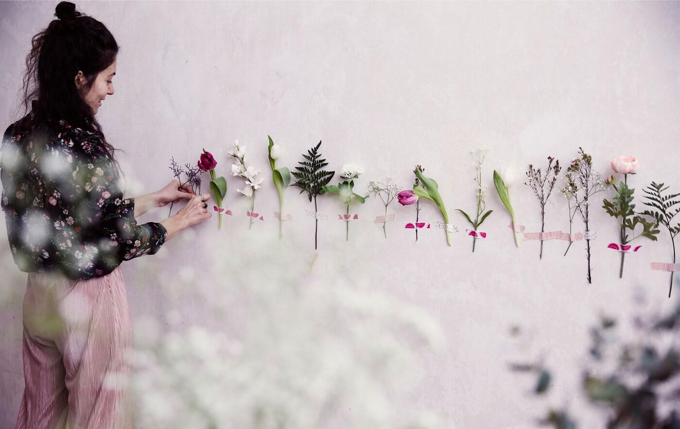 Julia tejpar fast enskilda blomstjälkar i en rad på en vit vägg.