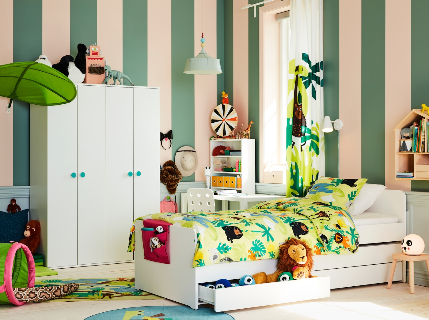 Jungle-themed children's room with a white bed frame, soft toys, green textiles with animal prints and a leaf-shaped canopy.