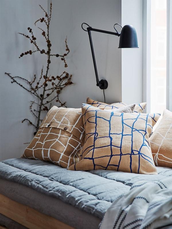 Junto a una ventana se ve un acogedor diván gris con cojines marrones estampados VÄRMER.