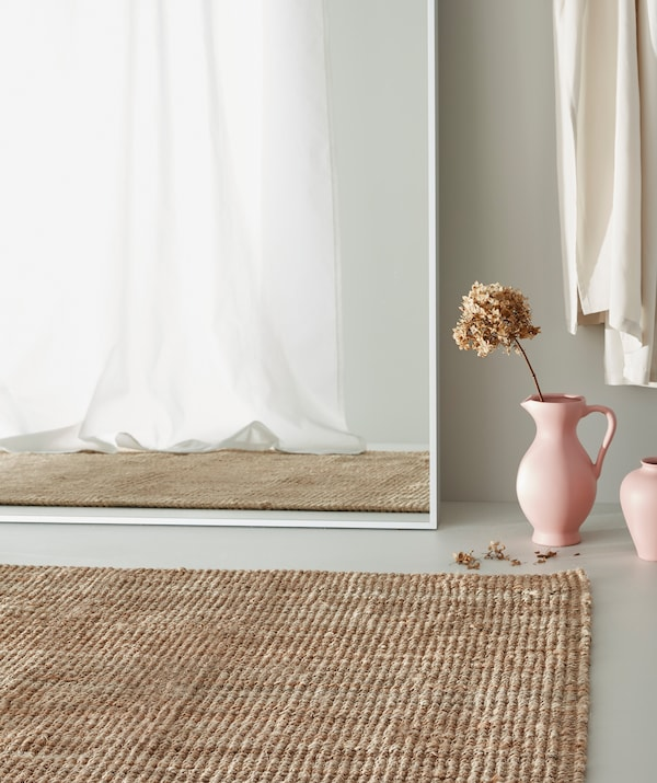Jute rug on a grey floor, pink vase with a dried flower standing next to a large white mirror showing a white curtain.
