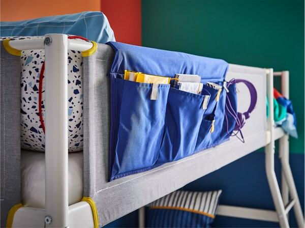جيب سرير أزرق يوضع على حاجز الحماية لسرير علوي أبيض/رمادي/أصفر.