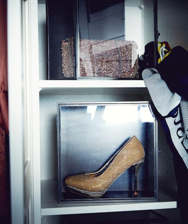 جزء من داخل خزانة ملابس مع رفوف تحمل صناديق عرض؛ واحد مع حقيبة يد لامعة، والآخر حذاء بكعب رفيع.