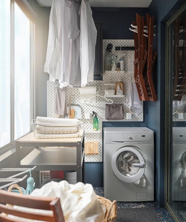 جزء من شرفة تم تحويله إلى غرفة غسيل صغيرة، مع غسالة ملابس وإكسسوارات مثبتة على الحائط وملابس معلّقة لتجف.