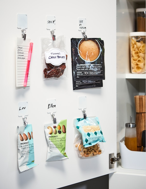 Kaapin ovi toimii säilytyspaikkana kevyille esineille. Valkoiset IKEA PLUTT -muovikoukut ja hopeanväriset RIKTIG-nipistimet toimivat ovien sisäpuolilla.