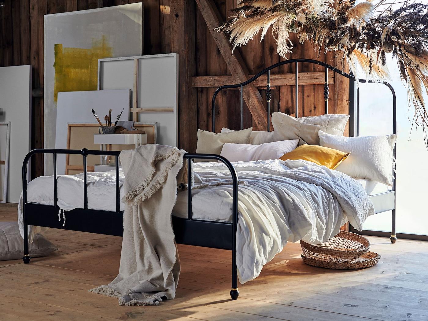 Kaareva ja ilmava SAGSTUA sänky, joka on tehty mustaksi maalatusta teräksestä, on kuvattu rustiikkisessa loft-asunnossa. Sängyssä on korkea pääty ja helposti yhdisteltävä ulkonäkö.