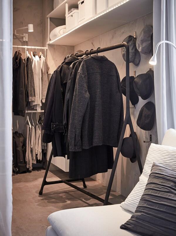 Kabáty a bundy zavěšené na věšáku, vzadu na zdi visí klobouky