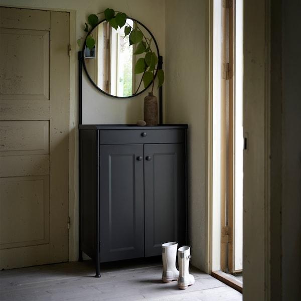 Kabinet bercermin KORNSJÖ berwarna hitam terletak di ruang depan dengan but berwarna kelabu di sebelahnya.