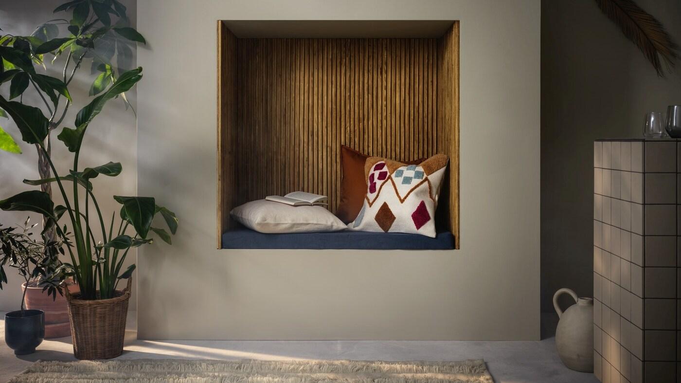 Kącik do czytania w ścianie ozdobiony poduszkami oraz stojącymi obok doniczkami z roślinami o dużych liściach z jednej strony i wazonem z drugiej.