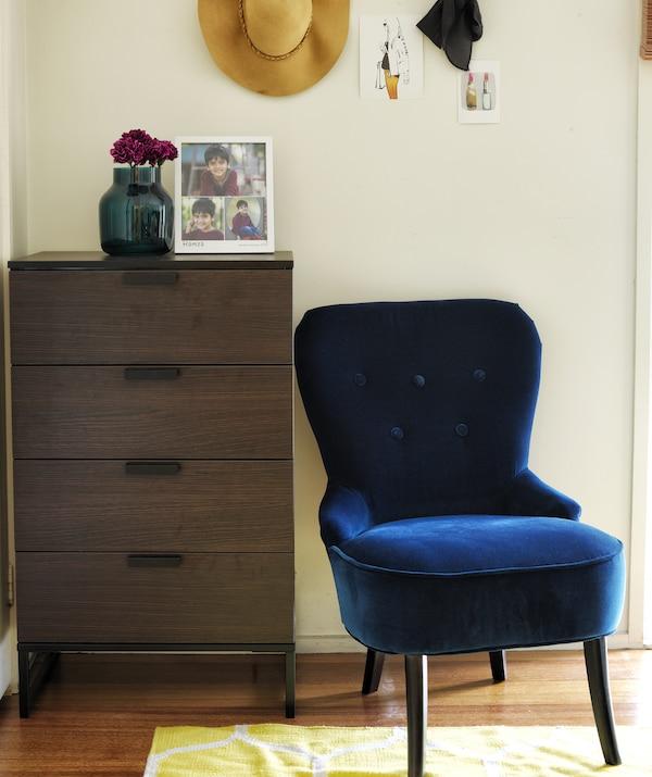 Kącik w białej sypialni z ciemną, drewnianą komodą i granatowym, aksamitnym fotelem.