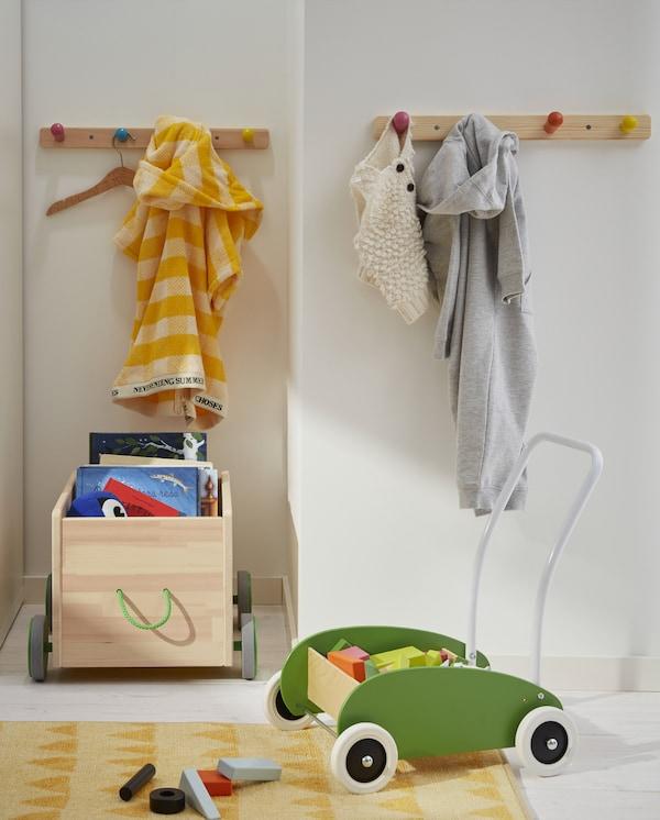 Kącik zabaw z zielonym wózkiem na zabawki, skrzynią na kółkach, żółtym dywanem, książkami, zabawkami i wieszakami z kolorowymi gałkami.