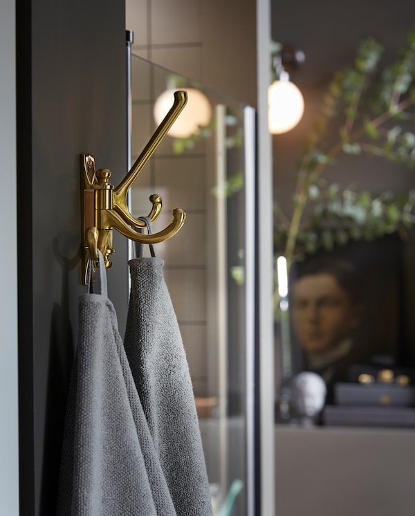 KÄMPIG 3-armed swivel hook in brass-colour is mounted on a wall next to a shower, and grey towels hang here to dry.