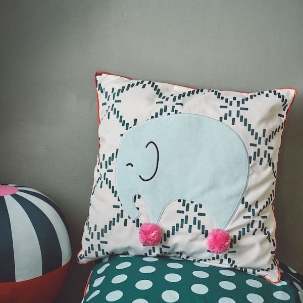 KÄPPHÄST cushion showing a green elephant with pink pompom feet against a dark green and white pattern.
