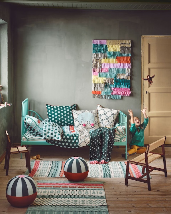 KÄPPHÄST duvet cover, rug, and cushions in a colourful room with a child throwing a toy monkey up in the air.
