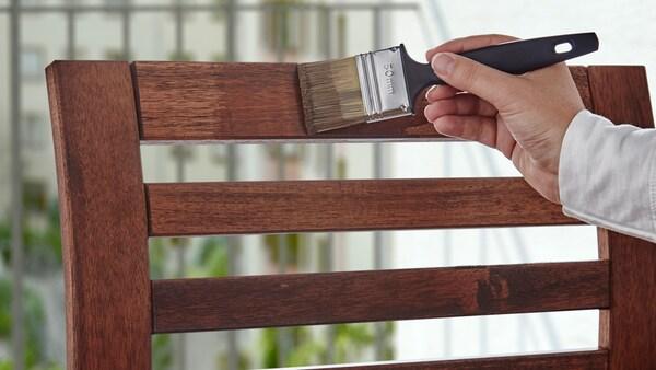 Käsi, joka pitelee maaliharjaa ja kyllästää puisen ulkotuolin takaosan petsillä.